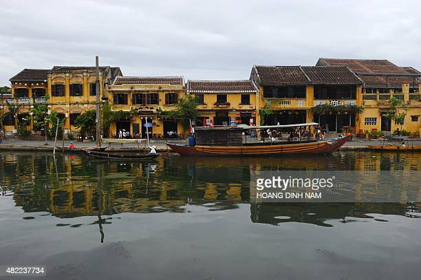 This picture taken on July 20 2015 shows boats anchored along the Hoai river in front of old houses in the UNESCOlisted town of Hoi An in the central...