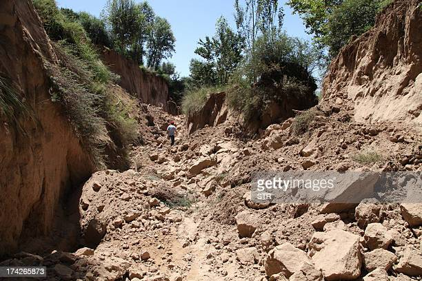 This picture taken on July 22 2013 shows a man walking over rocks and earth caused by an earthquake in the township of Zhongzhai in Minxian county in...