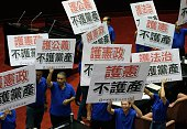 This picture taken on July 22 2016 shows Taiwanese legislators from the main opposition Kuomintang displaying placards reading 'protect the...