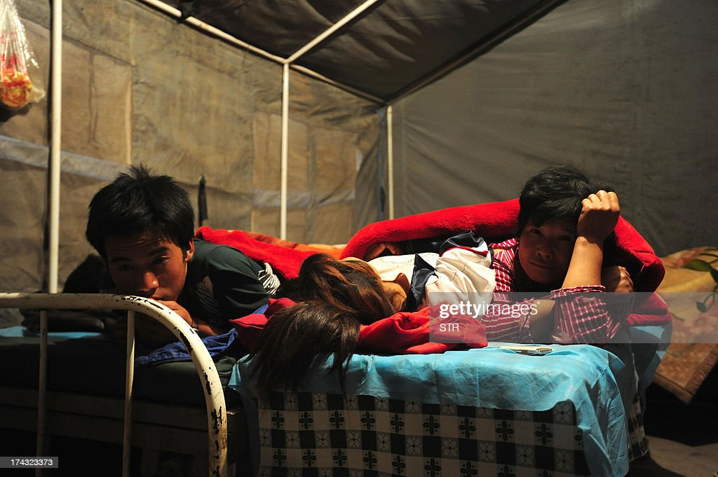 This picture taken on July 23, 2013 shows quake survivors lying in temporary shelter in Minxian county in Dingxi, northwest China's Gansu province. The traumatised survivors of two shallow earthquakes that killed at least 94 people in China began burying their dead on July 23, as they struggled with the devastation left behind. CHINA OUT AFP PHOTO