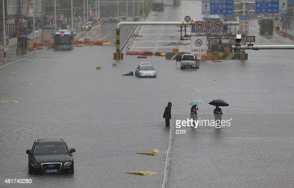 This picture taken on July 23 2015 shows a car trapped in floodwaters as residents try to cross the street in Wuhan in central China's Hubei province...