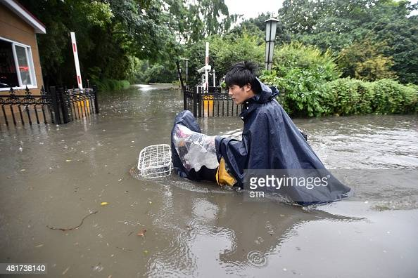 This picture taken on July 23 2015 shows a cyclist making his way through floodwaters in Wuhan in central China's Hubei province as strong storms hit...