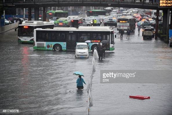 This picture taken on July 23 2015 shows a woman making her way through floodwater in Wuhan in central China's Hubei province as strong storms hit...