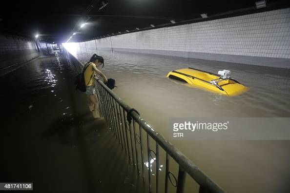 This picture taken on July 23 2015 shows a woman using a fence to make her way though a heavily flooded underpass in Wuhan in central China's Hubei...