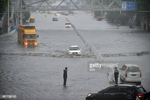 This picture taken on July 23 2015 shows cars making their way through floodwaters in Wuhan in central China's Hubei province as strong storms hit...