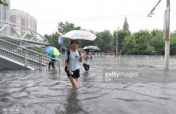 This picture taken on July 23 2015 shows residents making their way through floodwaters in Wuhan central China's Hubei province as strong storms hit...