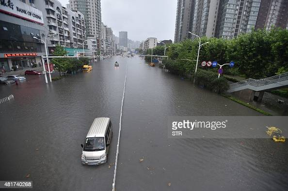 This picture taken on July 23 2015 shows vehicles making their way through floodwaters in Wuhan in central China's Hubei province as strong storms...