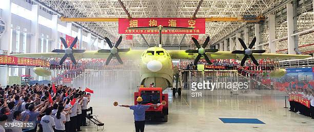 This picture taken on July 23 2016 shows a crowd waving flags during a ceremony to unveil the AG600 amphibious plane in Zhuhai in south China's...