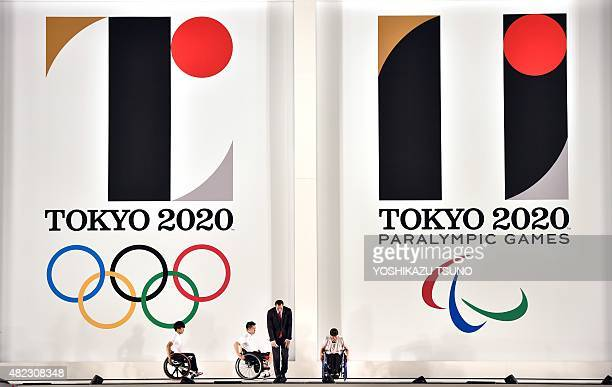 This picture taken on July 24 2015 shows hammer throw gold medalist Koji Murofushi and young athletes attending a ceremony to unveil the new logos of...