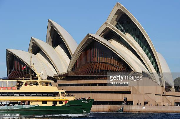 This picture taken on July 25 2012 shows a Sydney Harbour Manly ferry passing the Sydney Opera House in Sydney The iconic Australian landmark which...