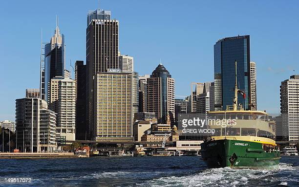 This picture taken on July 25 2012 shows a Sydney Harbour Manly ferry approaching the Circular Quay wharf alongside the city of Sydney Sydney...
