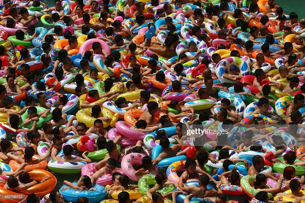This picture taken on July 25, 2014 shows people cooling off in a waterpark in Suining, southwest China's Sichuan province. Meteorological departments issued an orange alert for high temperature as a heat wave embraces Sichuan province, with temperature of most area topped 37 , local media reported. CHINA