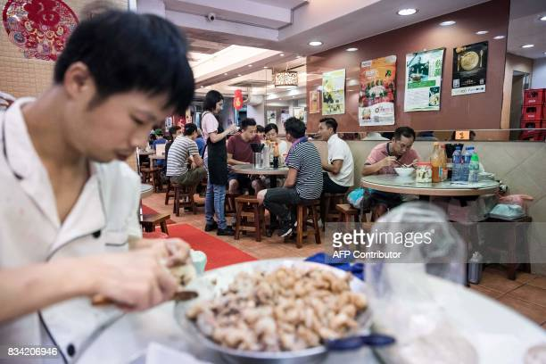 This picture taken on July 25 2017 shows a chef making dumplings as customers dine at a restaurant popular for its noodle dishes handmade using a...