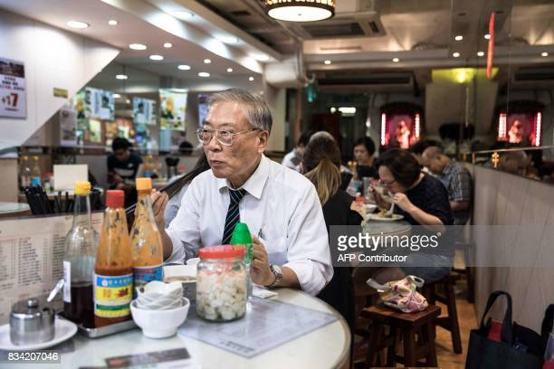 This picture taken on July 25 2017 shows a man eating at a restaurant popular for its noodle dishes handmade using a traditional bamboo pole...