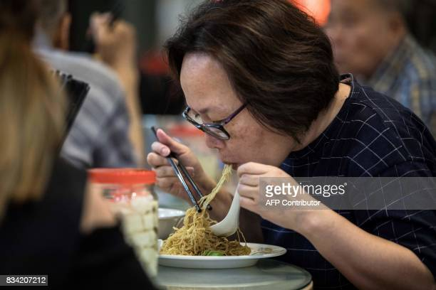 This picture taken on July 25 2017 shows a woman eating noodles handmade using a traditional bamboo pole technique at a restaurant in Hong Kong From...