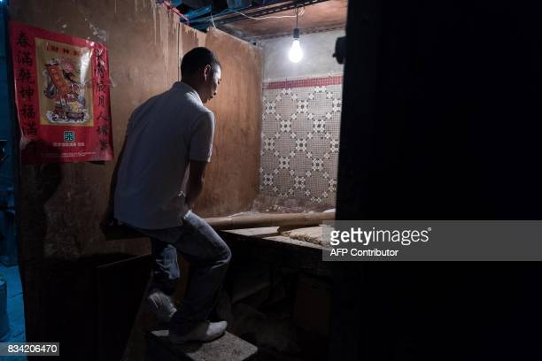 This picture taken on July 25 2017 shows Lau Fatcheong bouncing up and down on a bamboo pole to flatten the dough as he makes a batch of noodles in...