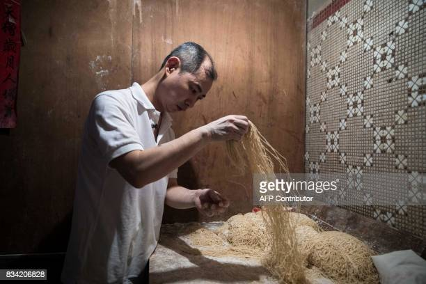 This picture taken on July 25 2017 shows Lau Fatcheong making a batch of noodles in Hong Kong From decadesold holes in the wall to multimillion...