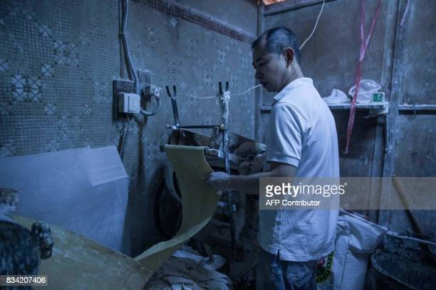 This picture taken on July 25 2017 shows Lau Fatcheong using a machine to flatten the dough as he makes a batch of noodles in Hong Kong From...