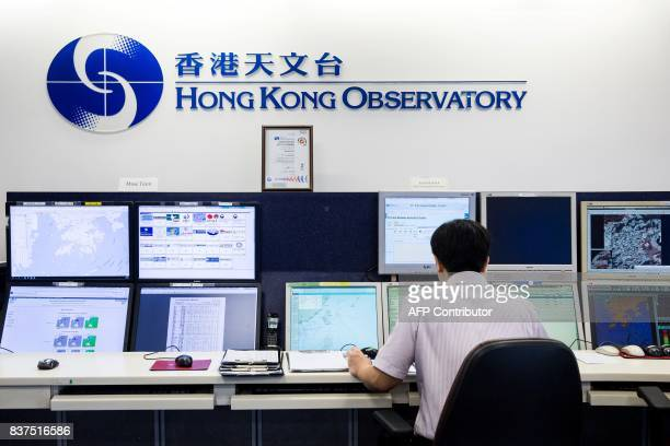 This picture taken on July 26 2017 shows an employee monitoring weather patterns at the Hong Kong Observatory headquarters in the Tsim Sha Tsui...