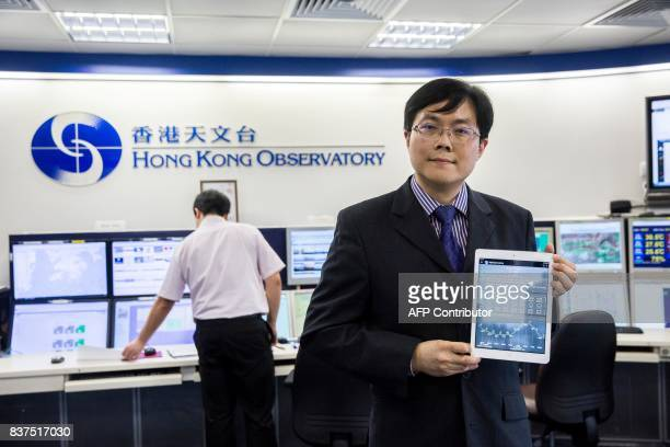 This picture taken on July 26 2017 shows an employee with the Hong Kong Observatory holding an iPad with the observatory's app open at their...