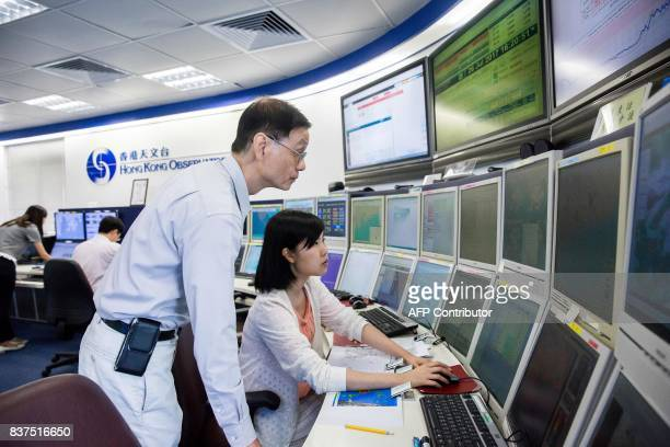 This picture taken on July 26 2017 shows employees monitoring weather patterns at the Hong Kong Observatory headquarters in the Tsim Sha Tsui...