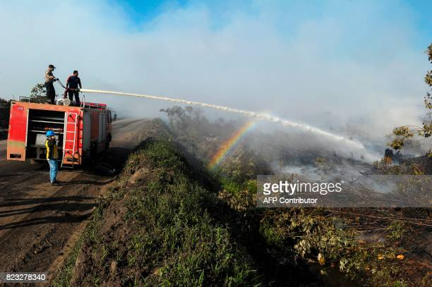 This picture taken on July 26 2017 shows Indonesian firefighters battling the peat forest fire at Meulaboh Aceh province In the past week about 35...