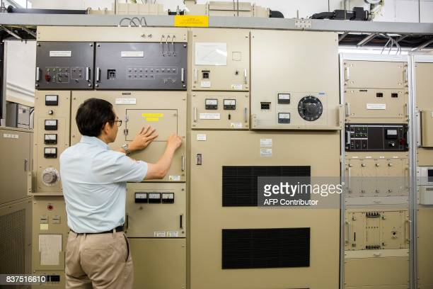 This picture taken on July 26 2017 shows senior radar specialist mechanic Ip Wingsing in the control room of the Ma On Shan radar station used for...