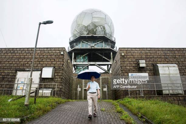 This picture taken on July 26 2017 shows senior radar specialist mechanic Ip Wingsing walking from the entrance of the Ma On Shan radar station used...