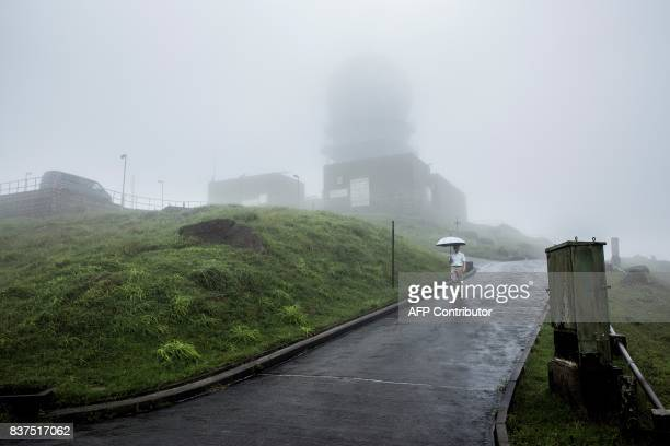 This picture taken on July 26 2017 shows senior radar specialist mechanic Ip Wingsing walking in foggy conditions near the Ma On Shan radar station...