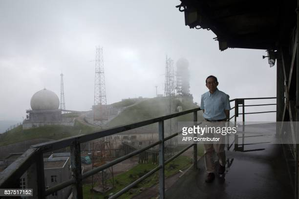 This picture taken on July 26 2017 shows senior radar specialist mechanic Ip Wingsing posing on a walkway under the radar component of the Ma On Shan...