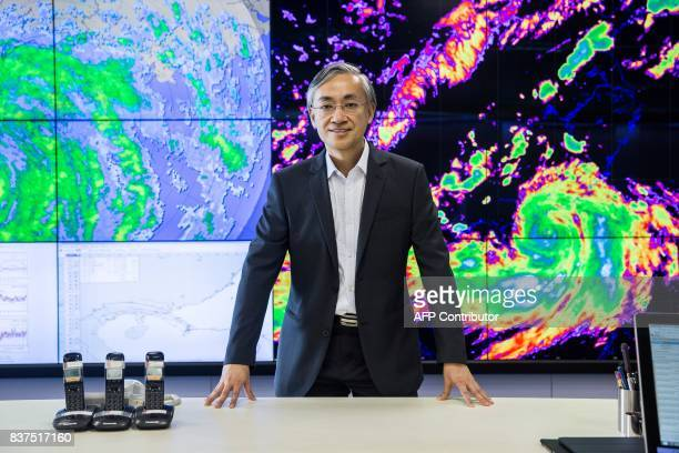 This picture taken on July 26 2017 shows the director of the Hong Kong Observatory Shun Chiming posing in front of imaging of a previous typhoon to...