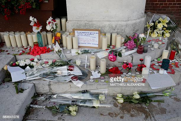 This picture taken on July 26 shows flowers candles and messages laid in front of the city hall in the Normandy city of SaintEtienneduRouvray on July...
