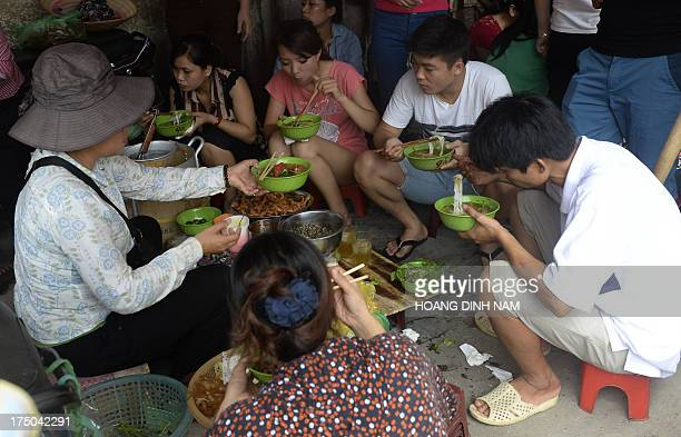 This picture taken on July 26 shows people eating noodles for lunch at a streetside food stall in downtown Hanoi Some 75 percent of tested rice...