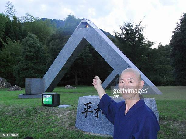 This picture taken on July 28 2008 shows Takudou Yamamoto displaying a flame that has been burning continuously since the 1945 atomic bombing of...