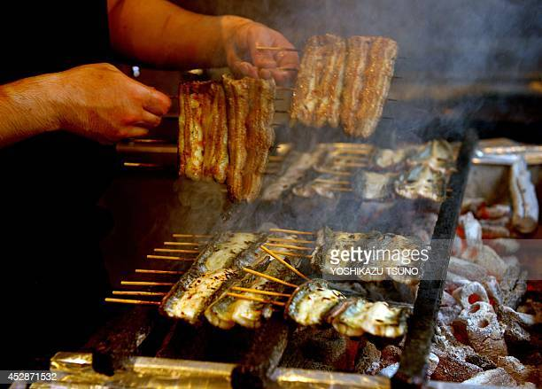 This picture taken on July 28 2014 shows an employee of a grilled eel restaurant Unatetsu grilling eels over charcoal fire in Tokyo one day before...