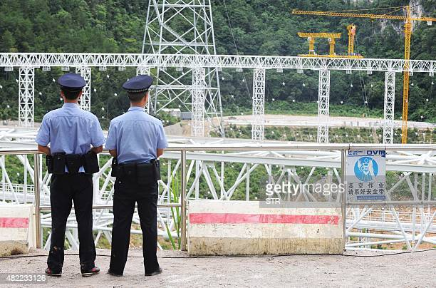 This picture taken on July 28 2015 shows security officials looking on at the construction site of the fivehundredmetre Aperture Spherical Radio...