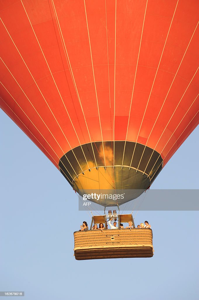 This picture taken on July 29, 2008 shows a hot air balloon flying over ancient ancient temple city of Luxor. A hot air balloon caught fire and exploded over Egypt's ancient temple city of Luxor during a sunrise flight on February 26, 2013, killing up to 19 tourists, including Asians and Europeans.