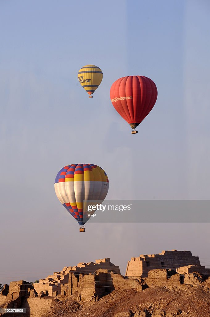 This picture taken on July 29, 2008 shows hot air balloons flying over ancient ancient temple city of Luxor. A hot air balloon caught fire and exploded over Egypt's ancient temple city of Luxor during a sunrise flight on February 26, 2013, killing up to 19 tourists, including Asians and Europeans.
