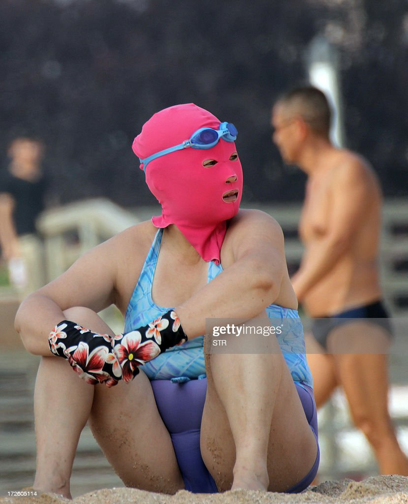This picture taken on July 3, 2013 shows a Chinese beachgoer wearing a body suit and protective head mask, dubbed 'face-kinis' by Chinese netizens, on a public beach in Qingdao, northeast China's Shandong province. The face masks were initially designed to protect from sunburn but it turns out they are also quite handy at repelling insects and jellyfish, as many people in China dislike getting a tan, especially on the face. CHINA OUT AFP PHOTO