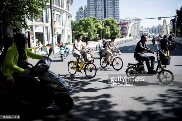 This picture taken on July 3 2017 in Shanghai shows a boy riding a bicycle from a sharing company Authorities in Shanghai and Tianjin will impose...