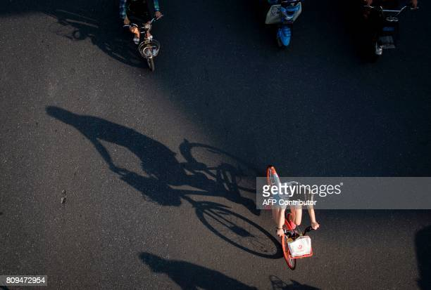 This picture taken on July 3 2017 in Shanghai shows a girl casting a shadow while riding a bicycle from a sharing company Authorities in Shanghai and...