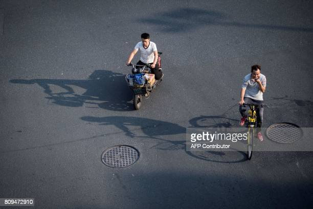 This picture taken on July 3 2017 in Shanghai shows a man riding a bicycle from a sharing company Authorities in Shanghai and Tianjin will impose...