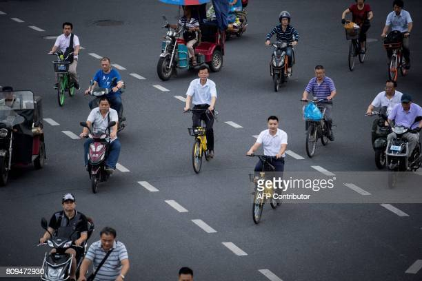 This picture taken on July 3 2017 in Shanghai shows two men riding bicycles from a sharing company Authorities in Shanghai and Tianjin will impose...