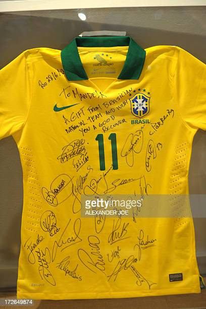 This picture taken on July 4 2013 shows a Brazilian football team jersey with players' autographs and messages that has been given on behalf of the...