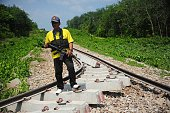 This picture taken on July 4 2016 shows an armed policeman guarding a railroad damaged by a bomb planted by suspected separatist militants in the...