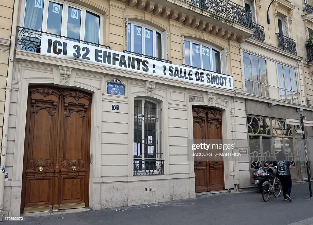 This picture taken on July 5, 2013 in Paris shows a banner reading in French 'Here 32 children : 1 drug room !,' to protest against France's first trial 'shooting gallery' which is supposed to be located in this building. The French government on February 5 authorised the opening of a trial 'shooting gallery' in the north of Paris, where addicts will legally be able to inject heroin and other drugs under medical supervision. AFP PHOTO/ JACQUES DEMARTHON