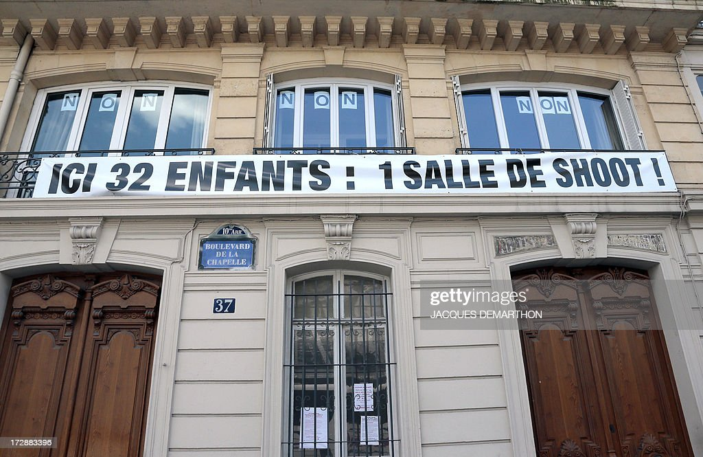 This picture taken on July 5, 2013 in Paris shows a banner reading in French 'Here 32 children : 1 drug room !,' to protest against France's first trial 'shooting gallery' which is supposed to be located in this building. The French government on February 5 authorised the opening of a trial 'shooting gallery' in the north of Paris, where addicts will legally be able to inject heroin and other drugs under medical supervision.