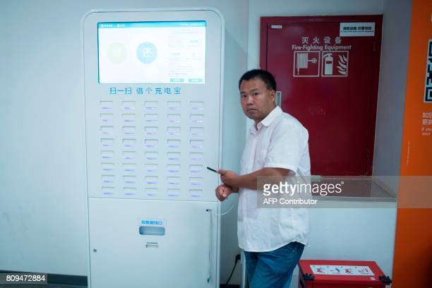 This picture taken on July 5 2017 in Shanghai shows a man charging his phone on a shared battery station inside a shop Authorities in Shanghai and...
