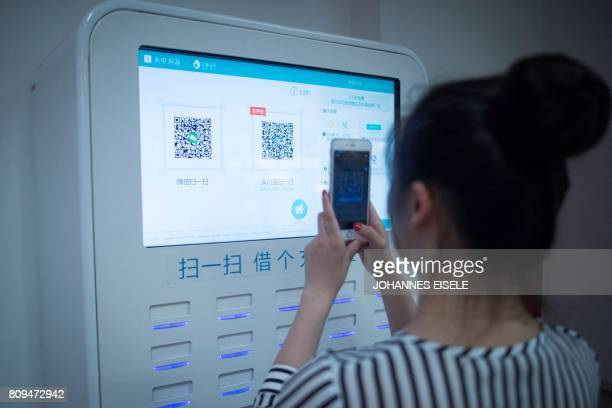 This picture taken on July 5 2017 in Shanghai shows a woman scanning a QR code on a shared battery station inside a shop Authorities in Shanghai and...