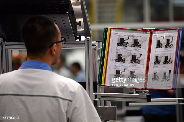 This picture taken on July 6 2014 shows a Chinese auto worker testing equipments at the RD department of the FAWVolkswagen plant in Chengdu southwest...